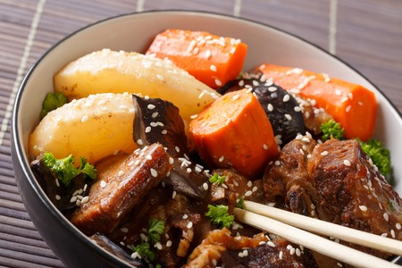 Korean cuisine: ribs stewed with mushrooms, pears and carrots close-up in a bowl. horizontal