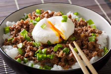 benedict: Japanese food: beef Soboro with egg poached, rice and green onion close-up in a bowl on the table. horizontal