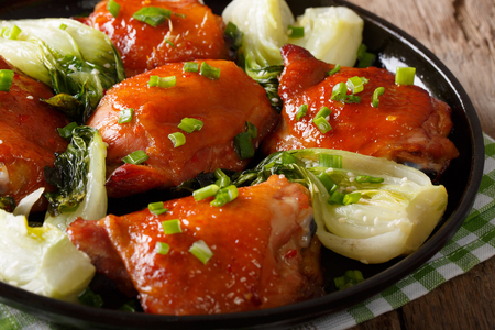 bok choy: Fried chicken thighs with bok choy and green onions close-up on a plate. horizontal Stock Photo