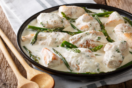 Stewed chicken with baby asparagus in a creamy sauce close-up on a plate on a table. horizontal