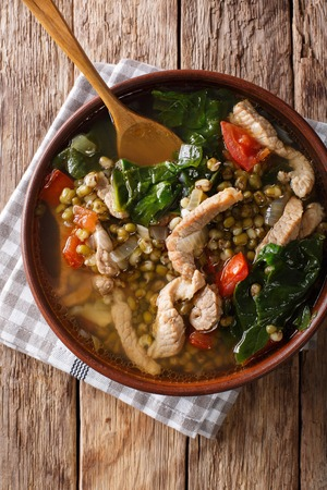 Philippine mung beans soup with pork closeup in a bowl on the table. Vertical top view from above