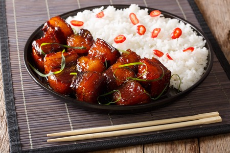 Vietnamese spicy caramel pork belly with rice closeup on a plate on a table. horizontal 스톡 콘텐츠
