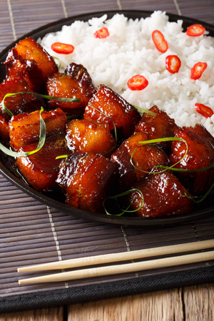 Glazed pork belly with rice garnish close-up on a plate on a table. vertical Stock Photo