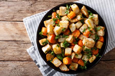 Gezond voedsel: gebakken selderiewortel en wortelenclose-up op een plaat op een lijst. Horizontaal bovenaanzicht van bovenaf Stockfoto