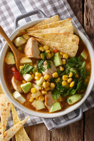 spicy tortilla soup with chicken, cilantro, tomatoes, avocado and corn close-up on the table. Vertical top view from above