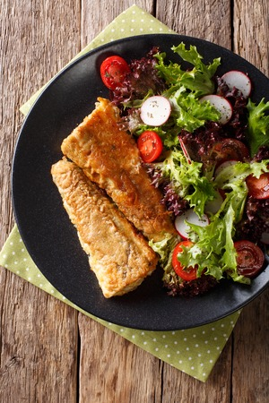 fried fish hake with salad from tomato, radish and lettuce close-up on a plate. Vertical top view from above  Stock Photo