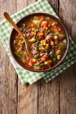 Sopa de verduras con primer plano de carne molida en un tazón sobre la mesa. Vista superior vertical desde arriba