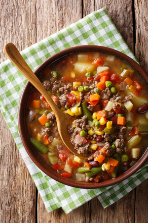 hamburger soup with ground beef and vegetables close-up in a bowl on the table. Vertical top view from above
