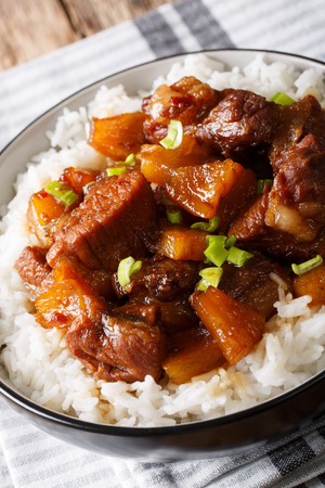 Philippine spicy pork Hamonado with pineapple and rice close-up on a plate. vertical