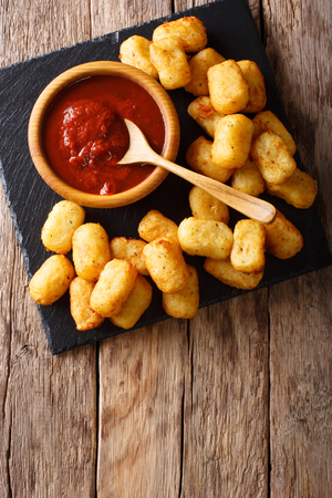 close up of rustic golden potato tater tots and ketchup on the table. Vertical top view from above