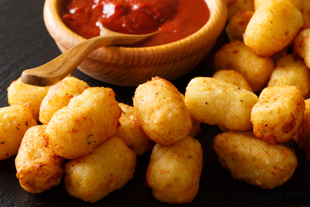 Homemade Tater Tots with tomato sauce close up on the table. horizontal