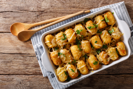 American Food: Tater Tots with cheese, meat, corn and parsley close-up in a baking dish on the table. horizontal top view from above