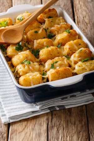 Homemade Baked Tater Tots with cheese, meat and greens close up in a baking dish on the table. vertical  Stock Photo