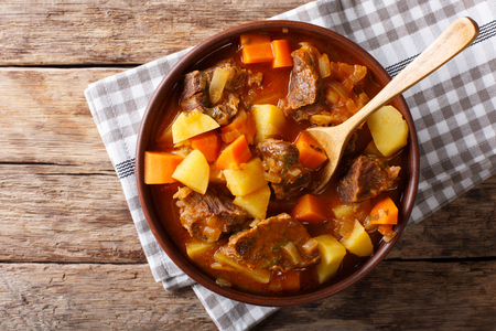 delicious stew estofado with beef and vegetables in a bowl close-up. Horizontal top view from above