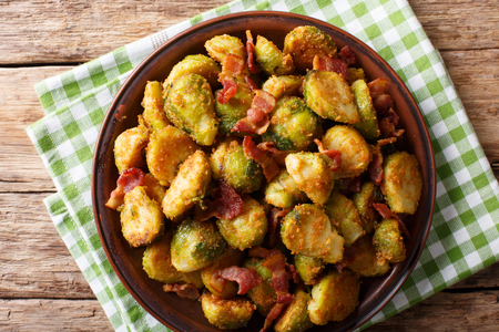 Delicious fried Brussels sprouts with crispy bacon close-up on a plate on a table. horizontal top view from above