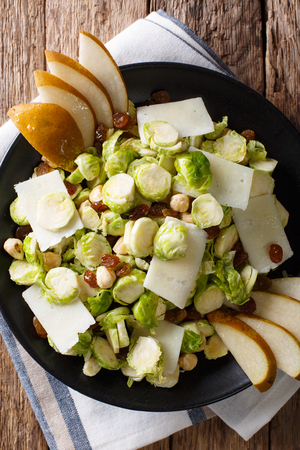 Organic salad from Brussels sprouts with hazelnuts, cheese, raisins and pears closeup on a plate. Vertical top view from above