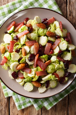 salad of fresh Brussels sprouts, dried cranberries, almonds and ham close-up on a plate. Vertical top view from above