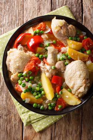 Pieces of chicken stew with potatoes, peppers, tomatoes, peas and onions close-up in a bowl on the table. Vertical top view from above Stock fotó