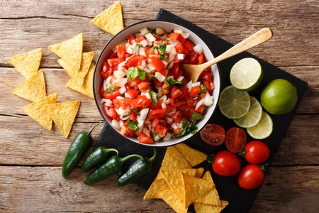Mexican appetizer Pico de Gallo close-up in a bowl on the table. horizontal top view from above