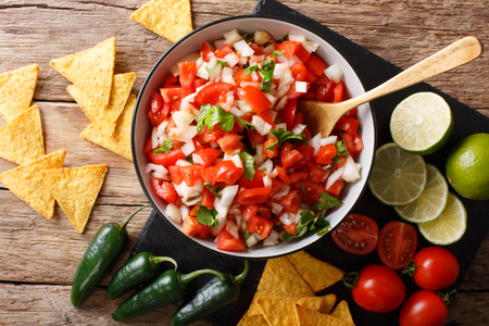 Homemade spicy pico de gallo close-up in a bowl and nachos on the table. Horizontal top view from above