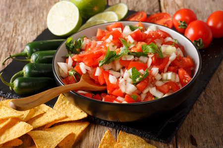 Mexican pico de gallo from tomatoes, onions, cilantro and jalapeno pepper close-up in a bowl and nachos on a table. horizontal