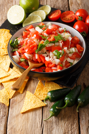 Homemade spicy pico de gallo close-up in a bowl and nachos on the table. vertical  Stock Photo