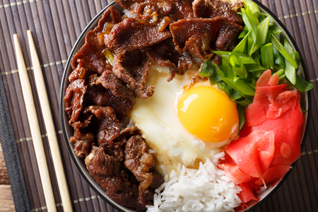 Japanese cuisine: gyudon beef with rice and onion in a bowl. horizontal top view from above