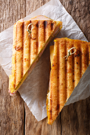 Grilled sandwich with ham, mustard, cheese, close-up on paper on the table. Vertical top view from above