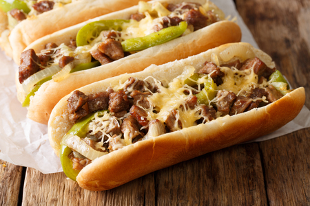 Philly cheese steak sandwich served on parchment paper close-up on the table. Horizontal Stock Photo