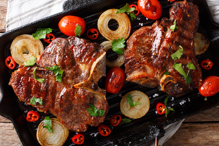T-Bone steak with tomatoes and onions in a grill frying pan close-up on a table. horizontal top view from above  Stock Photo