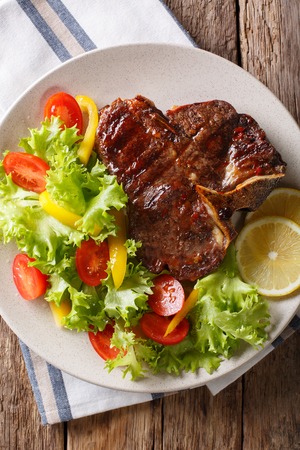T-bone beef steak with fresh vegetable salad closeup on a plate. Vertical top view from above Stock fotó