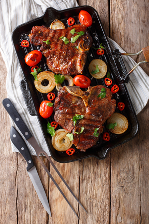 Delicious T Bone steak with grilled vegetables on the grill pan close-up on the table. Vertical top view from above Stock fotó