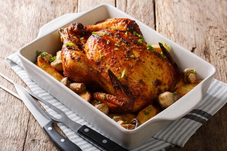 Beautiful crispy grilled chicken with mushrooms and potatoes close-up in a baking dish on a table. horizontal