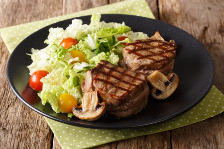 Healthy food: filet mignon steak with mushrooms and fresh vegetable salad close-up on a plate. horizontal
