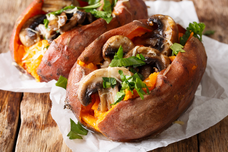 Baked whole sweet potato with mushrooms and cheese close-up on a parchment on the table. horizontal