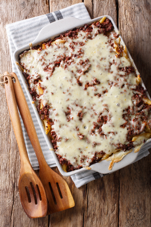 Delicious and hearty meal: million dollars pasta casserole with meat and cheese in a baking dish close-up on the table. vertical top view from above Stock Photo