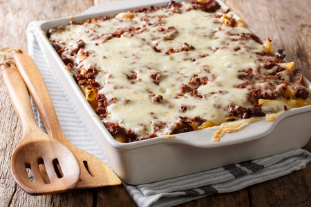 Million dollars pasta casserole with beef meat and cheese in a baking dish close-up on a table. Horizontal