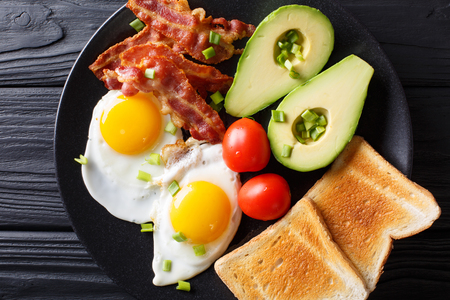 Delicious breakfast of eggs with crispy bacon, avocado, toast and tomatoes close-up on a black plate on the table. Horizontal top view from above