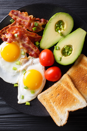 Homemade fried eggs with bacon, onion, avocado, toast and tomatoes close-up on a black plate on the table. Vertical top view from above