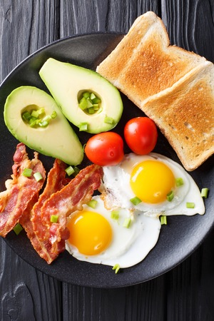 hearty breakfast: fried eggs with bacon, avocado, toast and tomatoes close-up on a plate on a table. Vertical top view from above