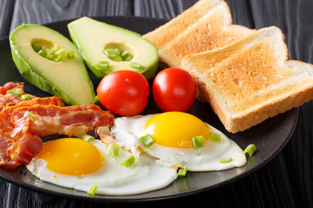 healthy traditional breakfast of fried eggs with bacon, fresh avocado, toast and tomato closeup on a black plate on the table. horizontal  Stock Photo