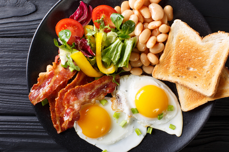 English homemade breakfast: fried eggs with bacon, beans, toast and fresh vegetables on a plate on the table. horizontal top view from above  Zdjęcie Seryjne