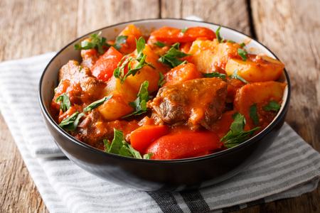 Slow Stew beef with potatoes, carrots, peppers in spicy sauce in a bowl on the table. horizontal