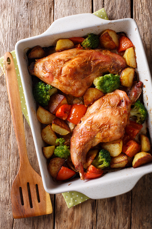 Delicious baked rabbit legs with potatoes, broccoli and tomatoes close-up in a baking dish on a table. Vertical top view from above