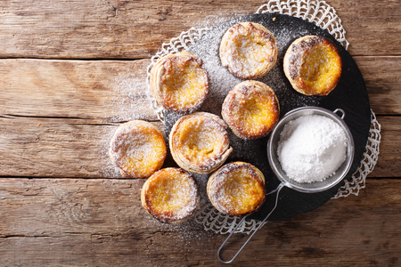 Fresh pastry dessert Pastel de nata with custard, sprinkled with powdered sugar close-up on the table. Horizontal top view from above