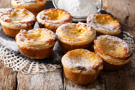 Delicious Pastel de Nata cakes stuffed with custard, sprinkled with powdered sugar close-up on the table. horizontal