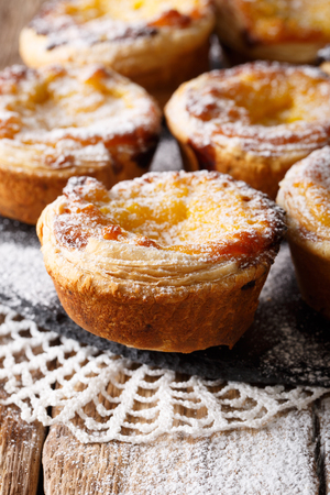 Freshly baked pastel de nata with powdered sugar close-up on the table. vertical  Stock Photo