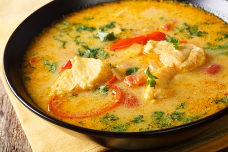 Brazilian fish Stew (Moqueca Baiana) with vegetables and coconut milk close-up on a plate on a table. Horizontal