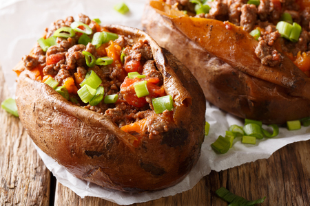 Healthy and tasty food baked sweet potato stuffed with ground beef and green onion close-up on paper on the table. horizontal