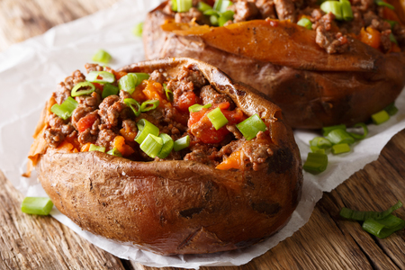Organic food: baked sweet potato stuffed with ground beef and green onion close-up on paper on the table. horizontal